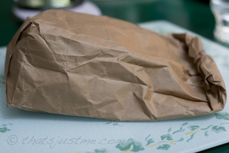 add kernels to paper bag and fold bag, leaving air inside.