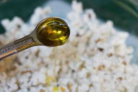 pour good quality olive oil over popped popcorn