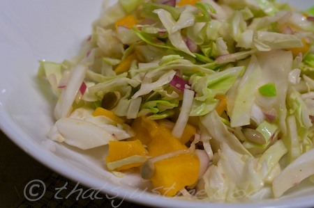cabbage mango salad with roasted pumpkin seeds and onions