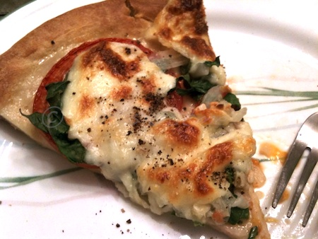 homemade pizza with onions, garlic, spinach, & cheese