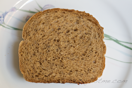 slice of fresh baked 100% whole wheat bread with caraway and poppy seeds